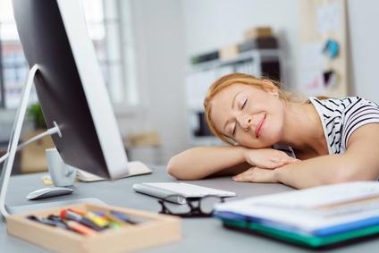 frau legt entspannt den kopf auf den schreibtisch