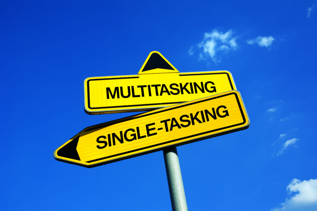 Multitasking vs Single-tasking - Traffic sign with two options - concentration and focus on one task and activity or effective and productive performance because of concurrence and simultaneity