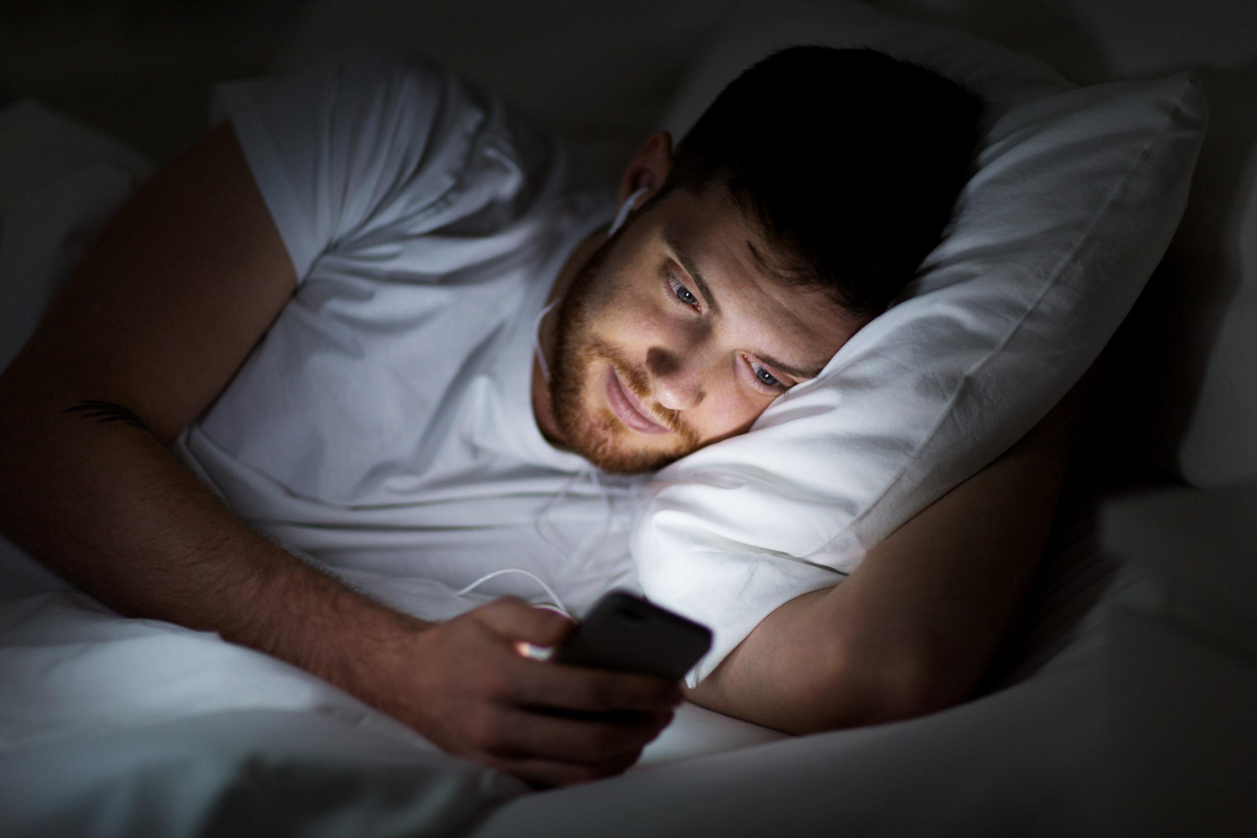 Mann mit Smartphone im Bett nachts